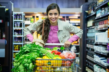 Portrait of woman with vegetables in shopping trolley