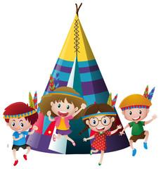 Four kids playing indian around teepee
