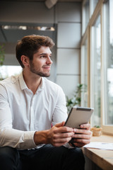 Smiling businessman sitting in cafe and using tablet computer