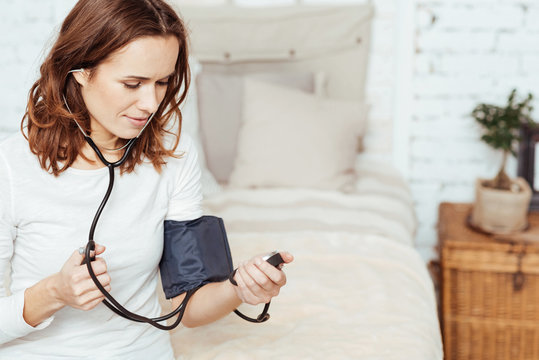 Pleasant concentrated woman measuring blood pressure