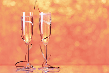 Two full champagne glasses with bokeh lights in the background