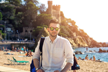 Handsome and confident hipster man in sun glasses with modern haircut and beard, wearing white shirt posing in sea beach scenery in Europe. Beautiful nature and old castle on the background.