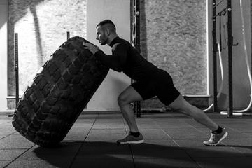 Strong handsome bodybuilder holding a huge tire