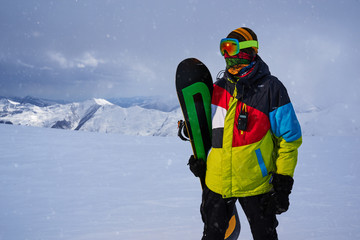 Snowboarder carries a board in  hands. Evening snowfall in  mountains.