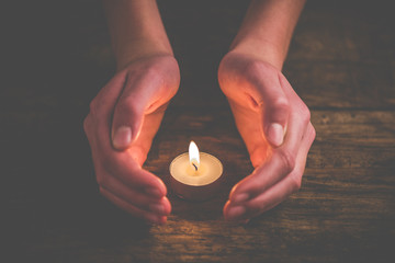 hands that protect the flame of a candle