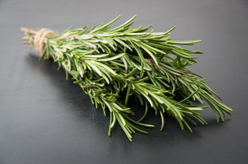 Sprigs of rosemary tied with string on a dark black background.