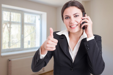 Portrait of happy female broker showing thumb up