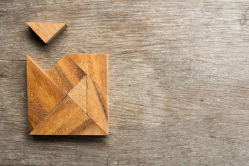 Wooden tangram with one piece is wait to fulfill the square shap