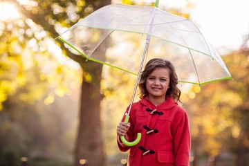 Portrait of cute girl with umbrella at park