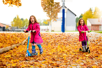 Twin girls in pink coat riding scooter on maple leaves.