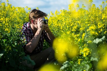 Man taking picture from camera in mustard field