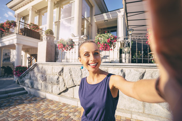 Traveling concept. Youth and technology. Young smiling woman taking selfie while walking by summer street.