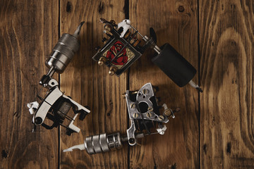 Three custom made professional induction tattoo machines arranged in round on a brown wooden table, top view