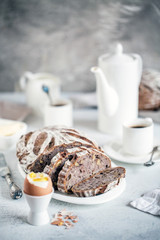 Artisan sourdough bread with rye flakes and walnuts in light breakfast composition with white porcelain, coffee, butter and hard-boiled egg
