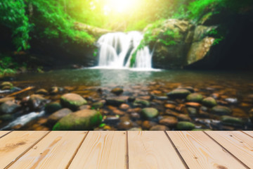 ooden board empty table in front of blurred background. Perspective brown wood over waterfall and creek in deep forest with flare of sun light   for mock up  display  montage your products, vintage.