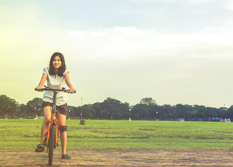 young woman riding a bicycle in a park., healthy lifestyles