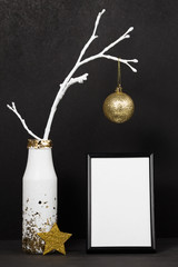 Christmas mock up with frame for poster, white branch of tree, star, golden christmas ball. Black background