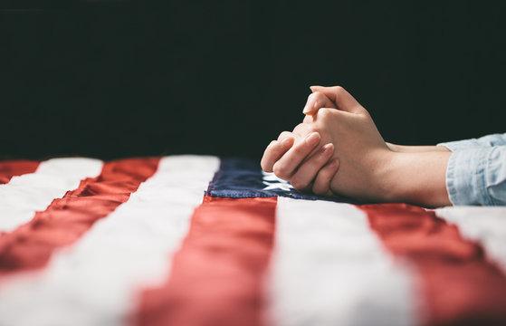Hands praying over USA flag
