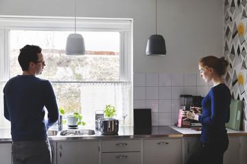 Man washing utensils while woman cooking food in kitchen