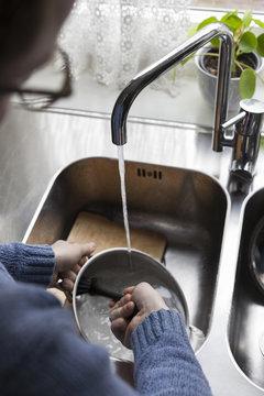 Cropped image of man washing utensils at home