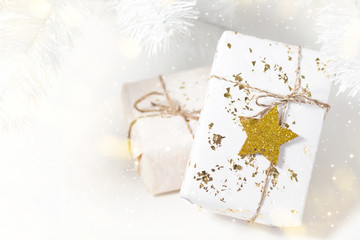 Light background with Christmas presents, white gift box with golden star, selective focus