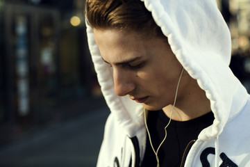 Close-up of teenage boy wearing hooded shirt listening music through headphones