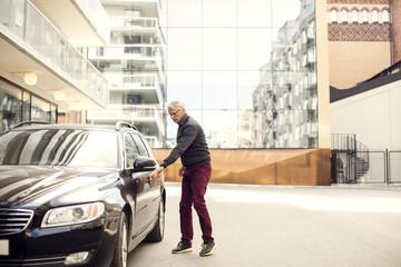 Senior man standing by car against buildings in city