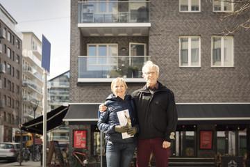 Portrait of smiling senior couple standing against building