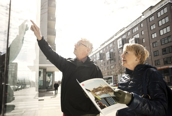 Senior woman reading catalog while man pointing on glass window in city