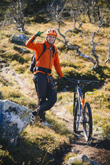 Portrait of man gesturing thumbs up while standing with mountain bike on hill
