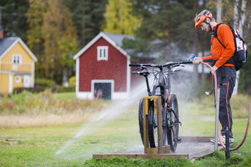 Man cleaning mountain bikes by splashing water from hose on grassy field