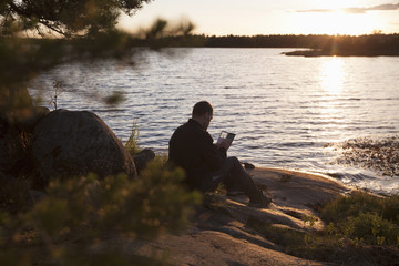 Man using smart phone while resting on rock against lake