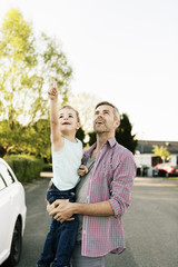 Son pointing up and showing to father while standing by car on street