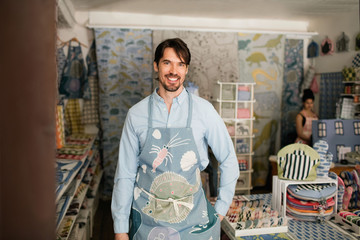 Portrait of smiling male owner standing with hand on hip while colleague working in fabric shop
