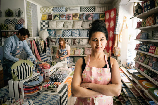 Portrait of confident owner standing with arms crossed while colleagues working in shop