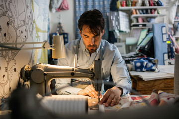 Serious male owner sewing fabric at shop
