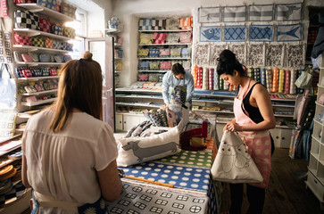 Male and female owners working in fabric shop