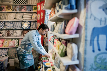 Side view of male owner arranging fabric on shelf at store