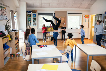 Students looking at male teacher performing handstand in classroom