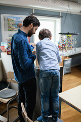 Rear view of teacher assisting male student in making project at school