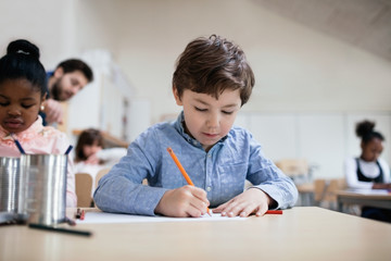 Serious boy studying while sitting in classroom at school