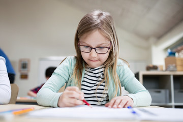 Concentrated girl wearing eyeglasses writing at classroom desk in school