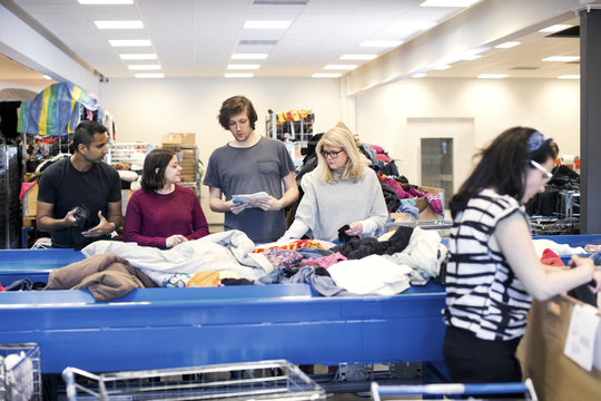 Volunteers listening to man while checking clothes on conveyor belt at workshop