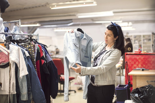 Serious female volunteer looking at jacket by clothes rack in workshop