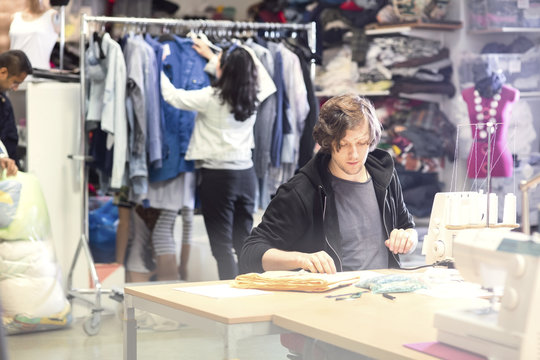 Man working on sewing machine while volunteer searching for clothes in rack at workshop