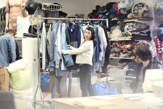 Woman talking to volunteer while searching for clothes in rack at workshop