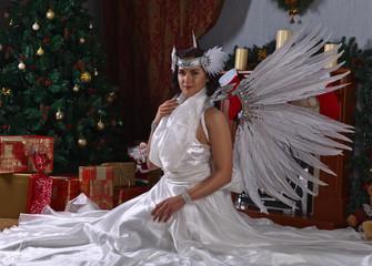 Woman in angel costume near Christmas tree