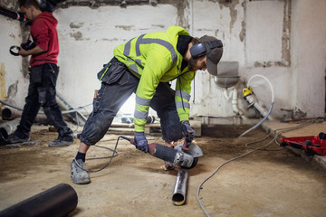 Plumbers working on pipes in abandoned basement