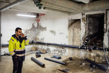 Man in protective clothing talking on phone in basement