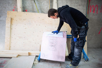 Manual worker reading blueprints at construction site